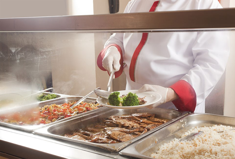 person serving meat and broccoli in buffet line