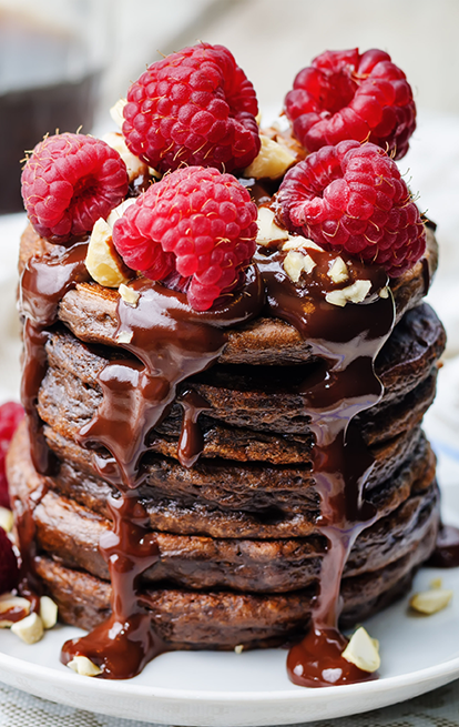 stack of chocolate pancakes with raspberries