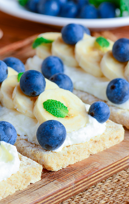 wafers with cheese spread topped with bananas and blueberries
