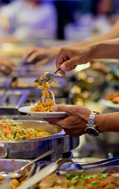 person serving a plate from a buffet line