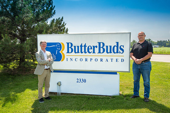 two guys standing next to butterbuds sign